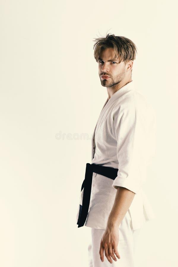 Гай представляет в белом кимоно с черным поясом Здоровый уклад жизни стоковое фото rf