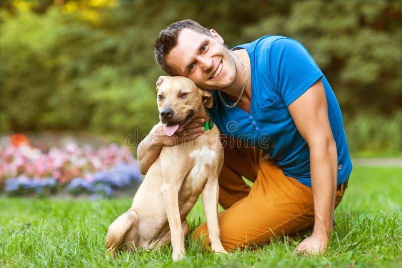 Гай при его собака обнимая в парке стоковое изображение