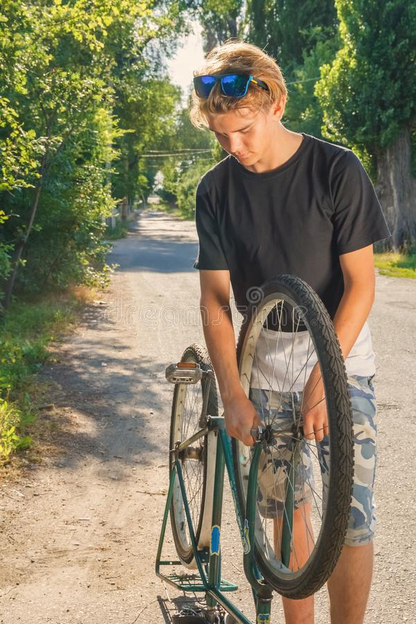 Гай ремонтирует велосипед на проселочной дороге в сельской местности в лучах захода солнца стоковая фотография
