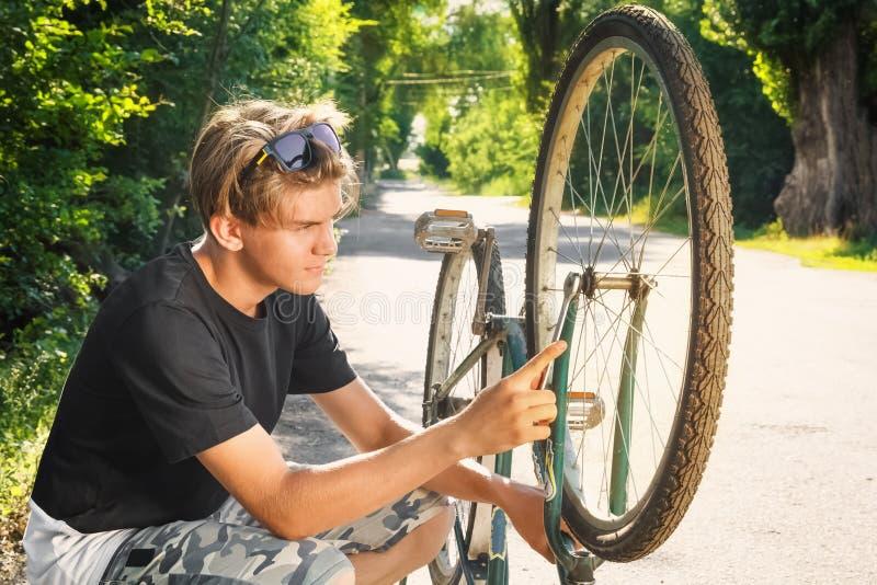 Гай ремонтирует велосипед на проселочной дороге стоковое фото rf