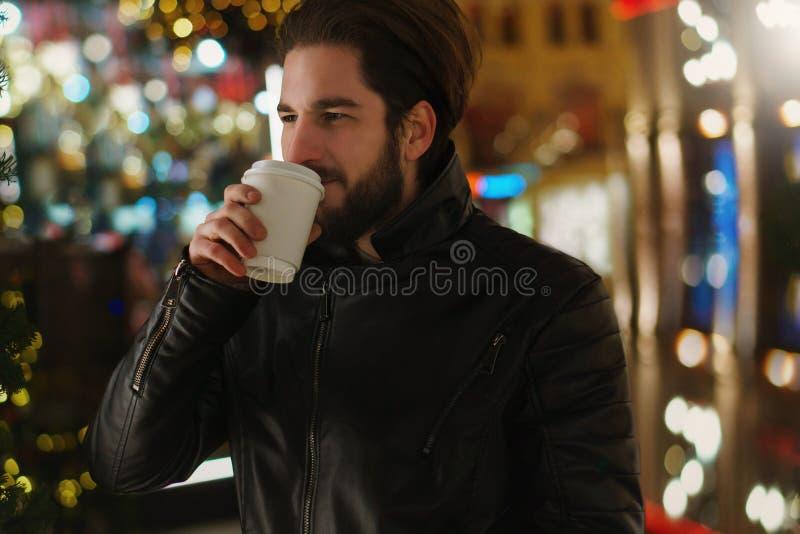 Гай с грея напитком праздничные света стоковые фото