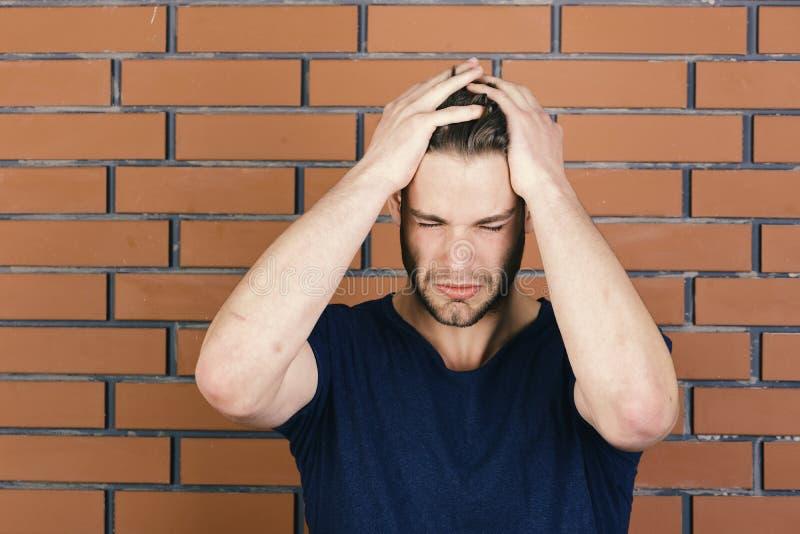 Гай с небольшой щетинкой в синих руках владением футболки на голове Мачо вымотанное из-за страдать от головной боли тело стоковая фотография rf
