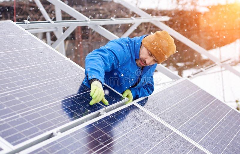 Гай с помощью инструментов устанавливает панели солнечных батарей, снежную погоду стоковая фотография