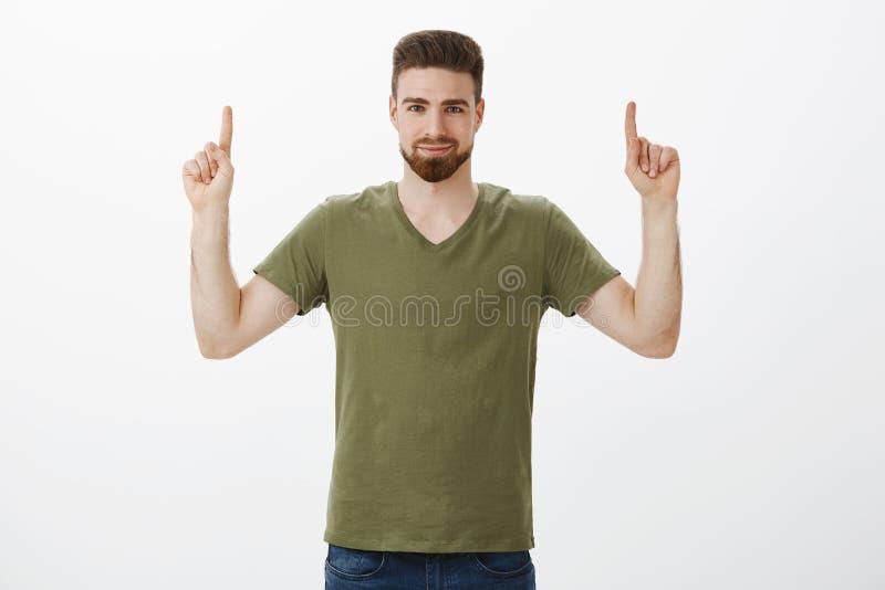 Гай уверил вас заканчивайте связь продукт, указывая с поднятыми указательными пальцами вверх на космос экземпляра с уверенной ухм стоковые изображения rf