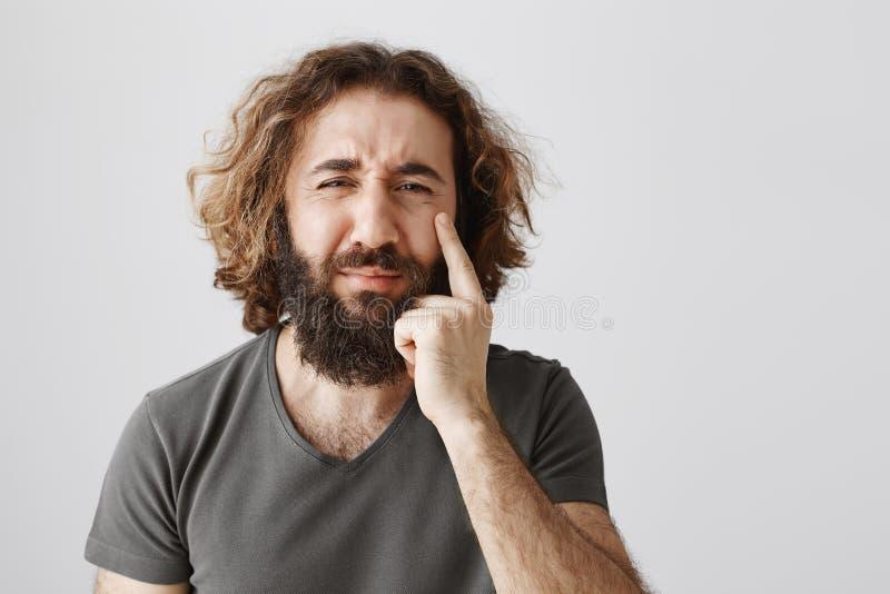 Гай хмуро что он стареет Портрет осадки пища восточный мужчина с бородой и вьющиеся волосы указывая на морщинку стоковое изображение