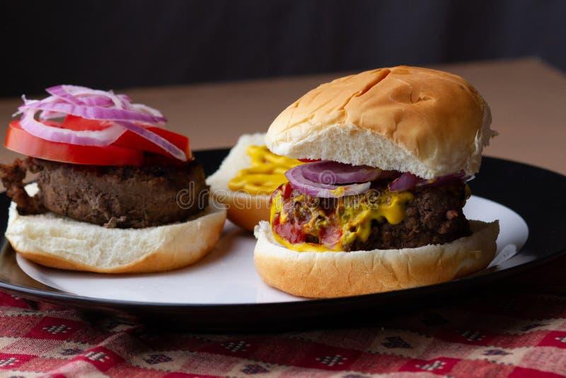 2 гамбургера на плите, одной открытой стороне стоковое фото