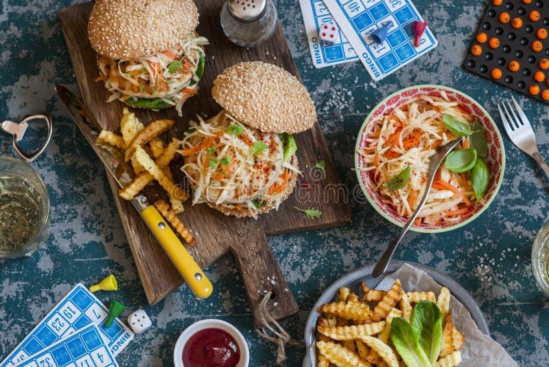 Гамбургеры с зажаренным slaw цыпленка и Коул на деревянной доске на таблице с карточками и bingo откалывают, взгляд сверху стоковые изображения rf