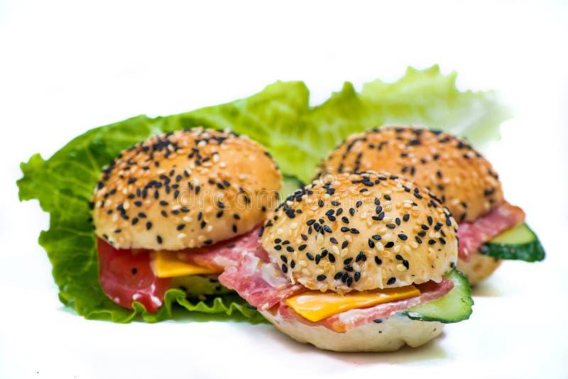 Гамбургеры с овощами и беконом на белой предпосылке стоковая фотография