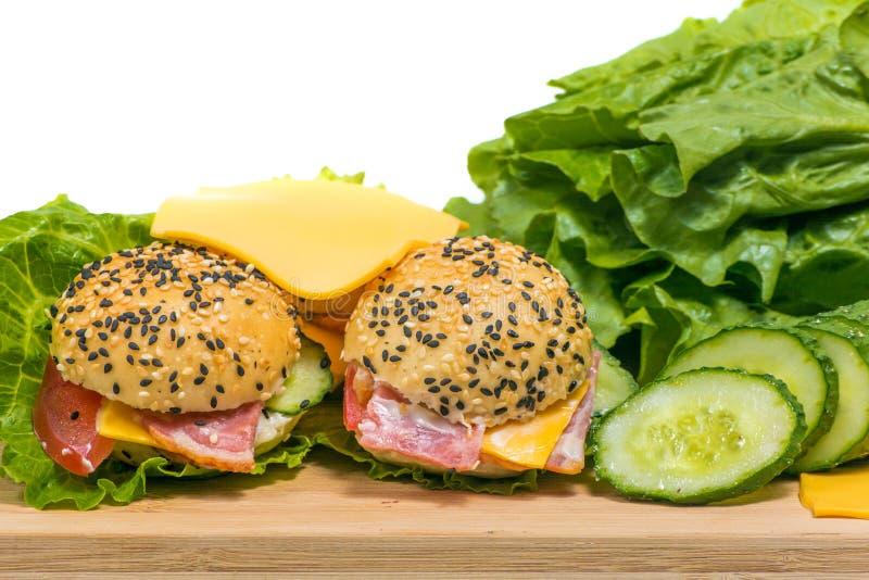 Гамбургеры с овощами и беконом на деревянном столе стоковая фотография