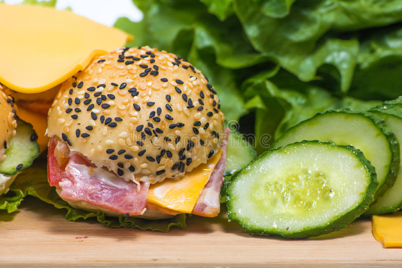 Гамбургеры с овощами и беконом на деревянном столе стоковое изображение rf