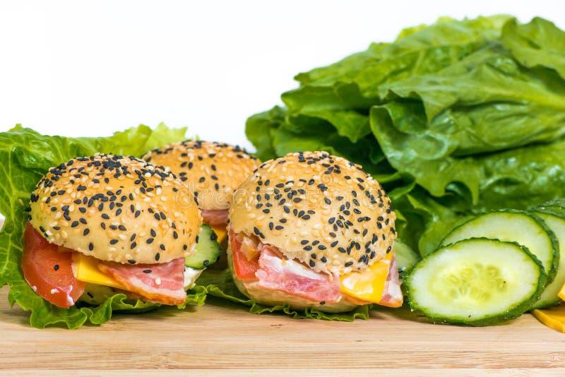 Гамбургеры с овощами и беконом на деревянном столе стоковые фотографии rf