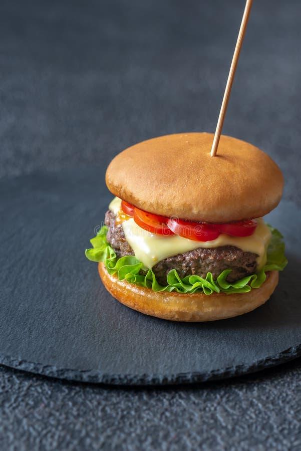 Гамбургер на черной каменной доске стоковое фото