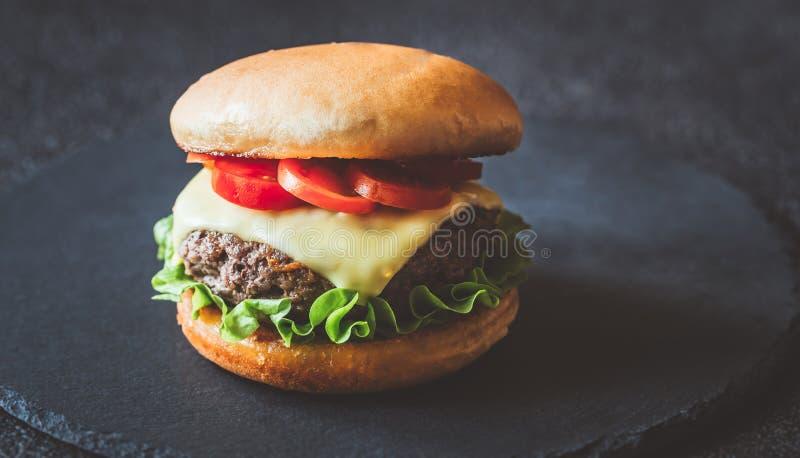Гамбургер на черной каменной доске стоковые изображения rf