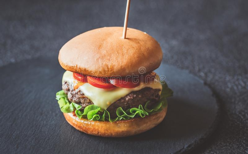 Гамбургер на черной каменной доске стоковое изображение rf