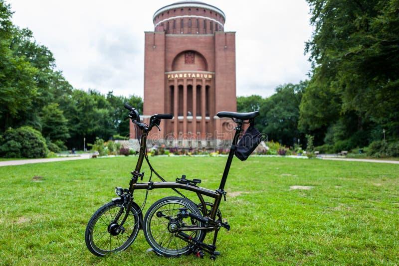 Гамбург, Германия - 14-ое июля 2018: Велосипед варианта лака черноты Brompton перед планетарием стоковое фото rf