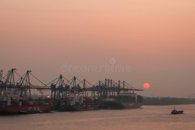 Гамбург, Германия - 14-ое мая 2014: Заход солнца на контейнерном терминале в порте Гамбурга которые регулируют около 90 миллионов стоковые изображения rf