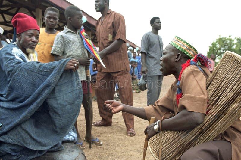 Ганский музыкант просит деньги к старейшине деревни стоковые фото