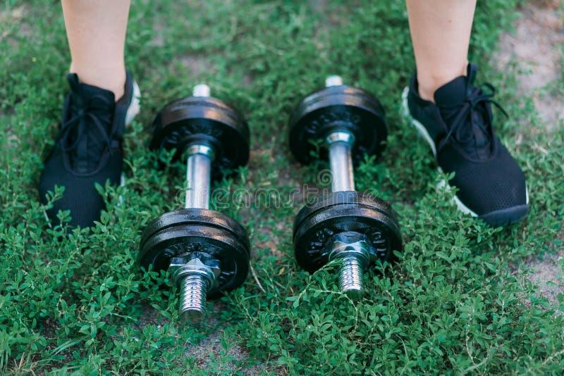 Гантели на предпосылке зеленой травы и foots в черных тапках стоковые фотографии rf