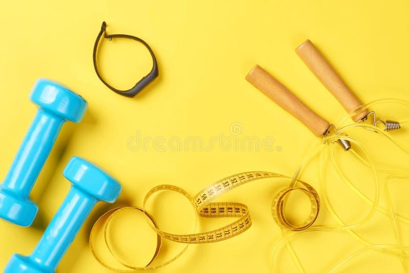 Гантели, отслежыватель фитнеса, веревочка скачки и измеряя лента на желтой предпосылке, концепция фитнеса стоковые фото