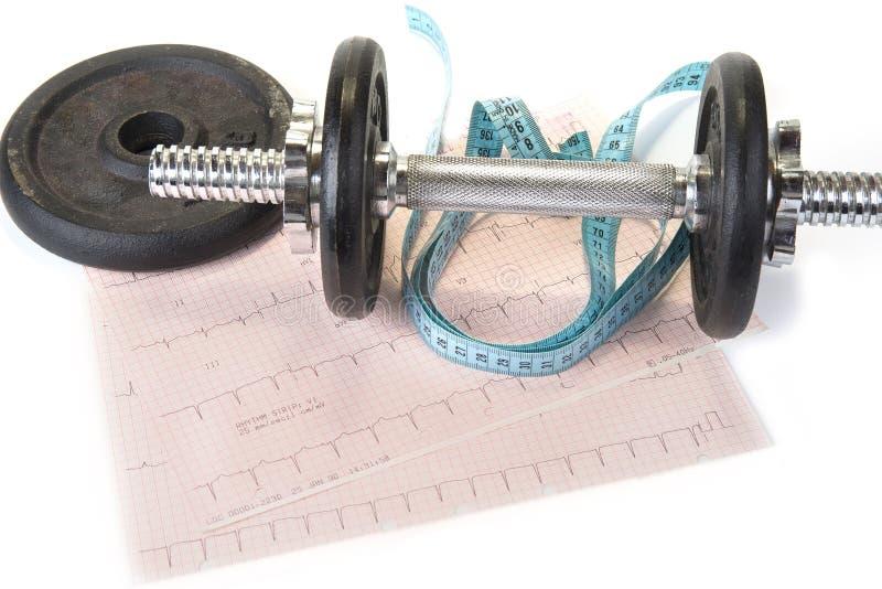 Гантели с лентой измерения и диаграммой EKG Здоровая тренировка делает более сильное сердце стоковое изображение