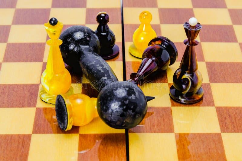 Гантель лежит на доске, на белом короле шахмат, чернота падала рядом Победа силы над разумом стоковая фотография