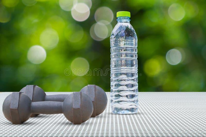 Гантели и взгляд со стороны бутылки с водой на алюминиевом поле на запачканной предпосылке bokeh стоковое фото rf