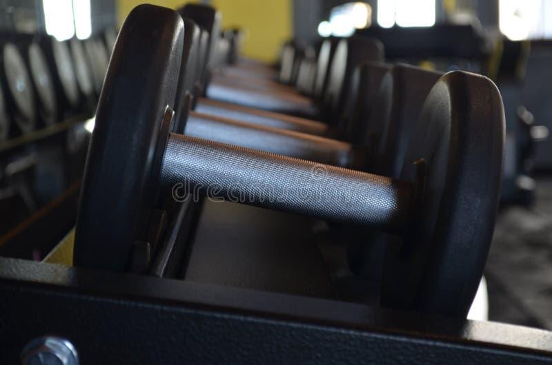 Гантели металла в ряд в спортзале стоковое фото rf