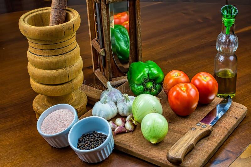 Гарик, лук, зеленый перец и помидоры на деревянной резке со стаканом оливкового масла, соли и черного перца в рамкинсах, wo стоковые фотографии rf