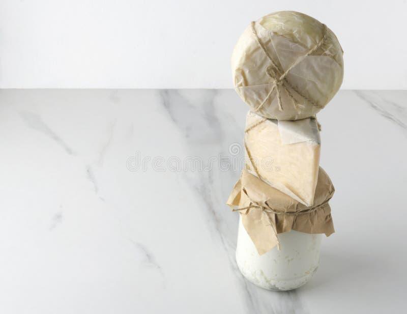 Гауда и provolone упакованные в бумаге eco, бумажном мешке на белой мраморной пирамиде таблицы нескольких очень вкусных видов сыр стоковое изображение