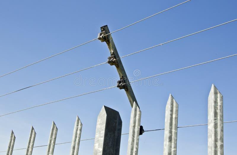 Гальванизированные поляки держа высоковольтную разделительную стену стоковая фотография rf