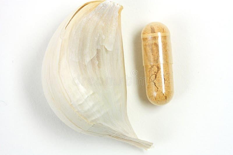 Гвоздика чеснока с таблеткой на белой предпосылке стоковое изображение rf