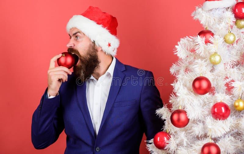 Где мои cookie Потребность в еде Аппетит и голод Чувствую себя голодным Санта-бородатый мужчина кусает красный христмас-мяч стоковые изображения rf