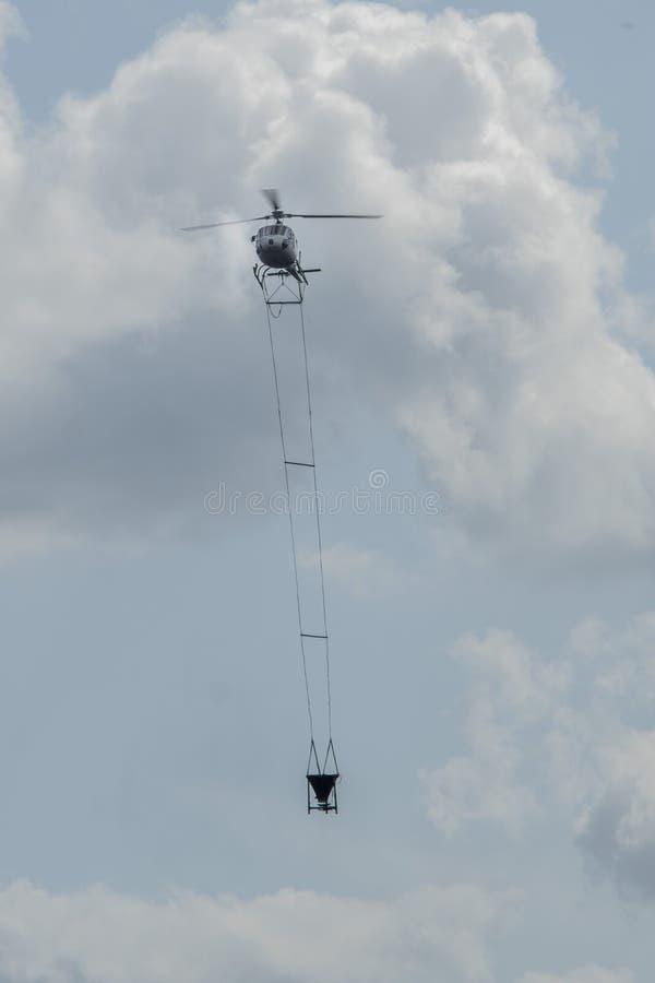 Геликптер летает с большой бочкой лайма над лесом стоковое фото rf