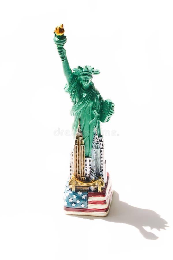 Генетическая статуя свободы и другие символы города и США Нью-Йорка NYC как дешевый сувенир с тенью изолированной дальше стоковое фото