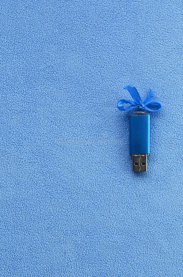Гениальная карточка флэш-память usb сини с голубым смычком лежит на одеяле мягкого и мехового света - голубой ткани ватки Классич стоковая фотография rf