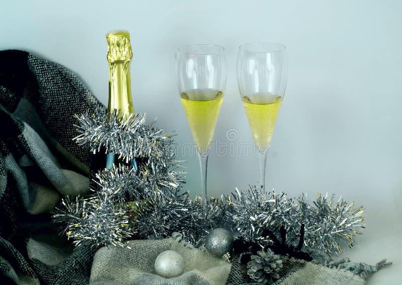 Гениальное оформление рождества Заполненные стекла и бутылка шампанского украшенные в праздничной теме на белой предпосылке Стиль стоковое изображение