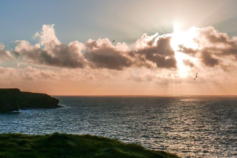 Гениальное сверкающее солнце устанавливает вдоль изрезанного побережья полуострова головы петли ` s Ирландии, графства Клары, Ирл стоковая фотография