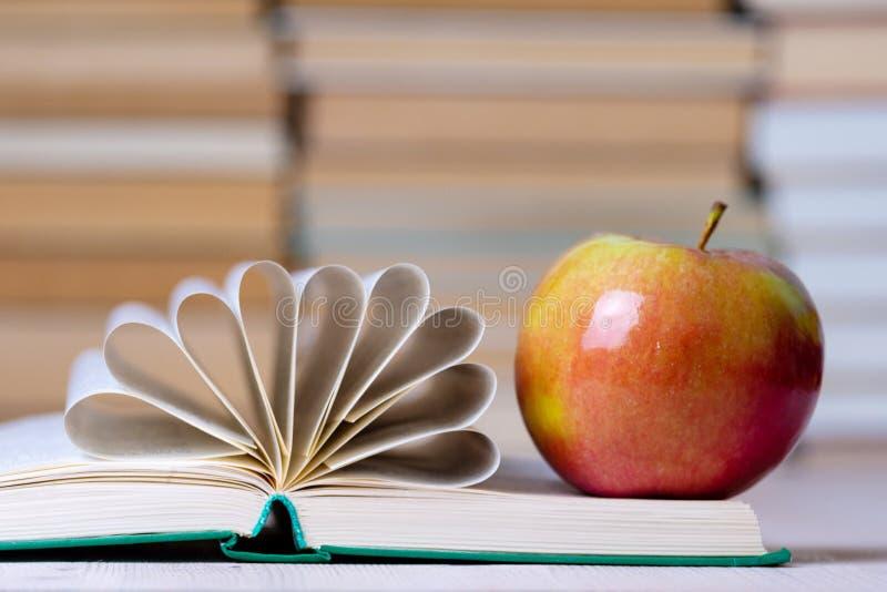 Гениальное яблоко с пирофакелом на своей стороне и открытой книге, страницы собрано в центре и согнуто стоковая фотография