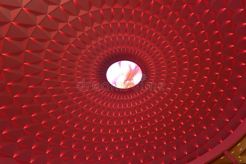 Геометрическая картина на круговой верхней части современного здания осветила красными светами приведенными, освещением ландшафта стоковые фото