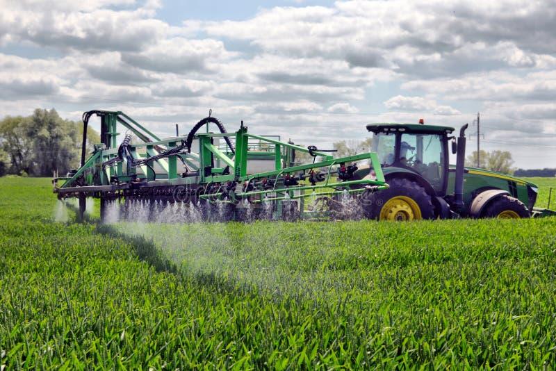 Гербициды пшеничного поля фермера распыляя стоковое изображение