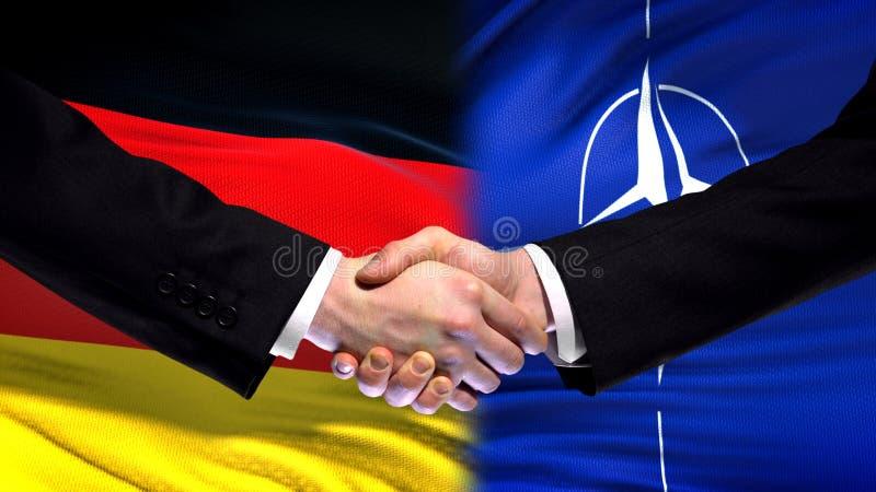 Германия и рукопожатие НАТО, международные отношения приятельства, предпосылка флага стоковое изображение