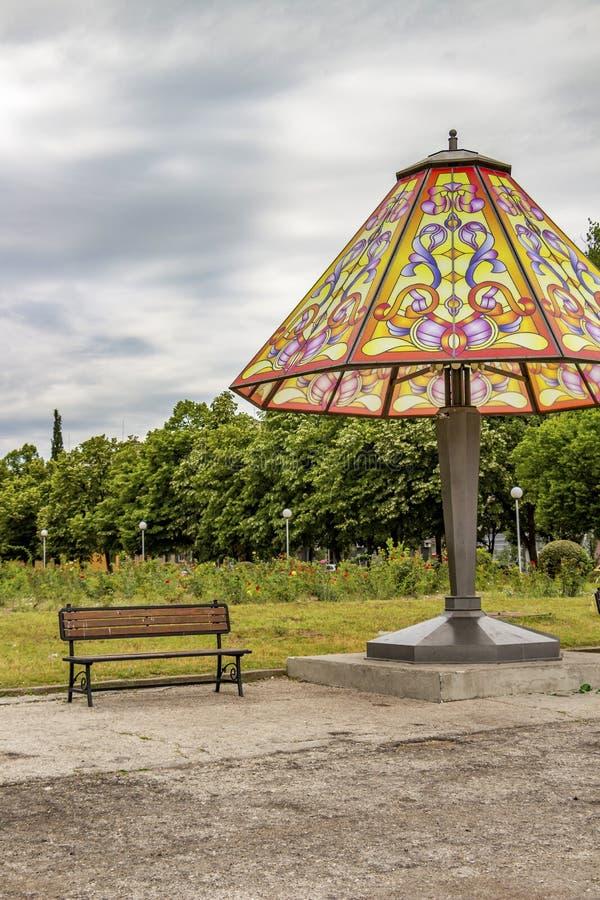 Гигантская лампа ухода за больным и стенд в общественном парке под небом лета overcast стоковое изображение rf