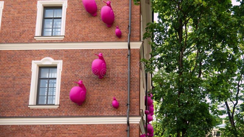 Гигантские розовые улитки взбираются на здании стоковая фотография