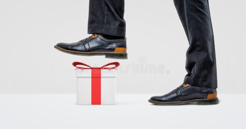 Гигантский ботинок бизнесмена готовый для того чтобы шагнуть на белую подарочную коробку с красным смычком стоковые фотографии rf