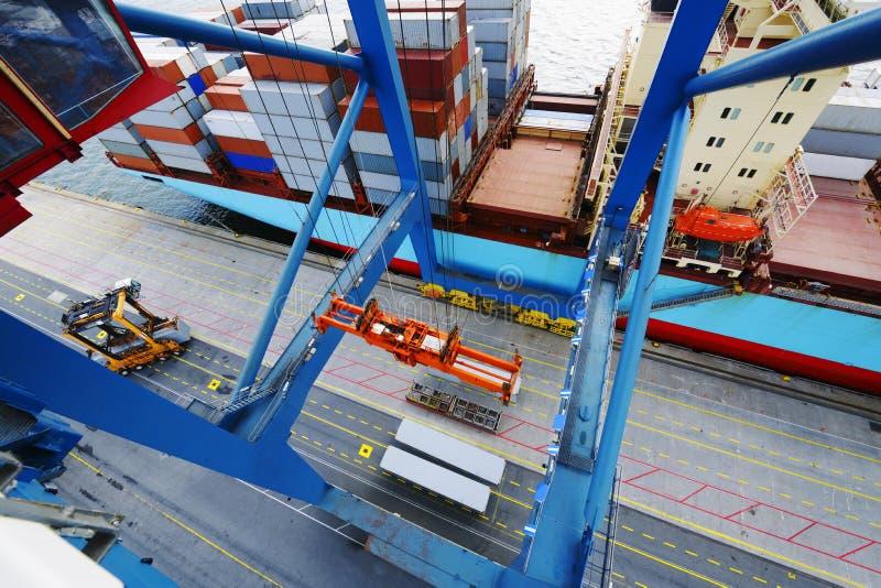 Гигантский кран нагружая контейнеровоз в порте стоковые изображения