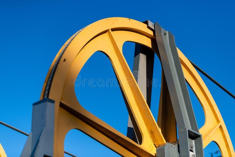 Гигантское желтое колесо шкива на фуникулере стоковые фотографии rf