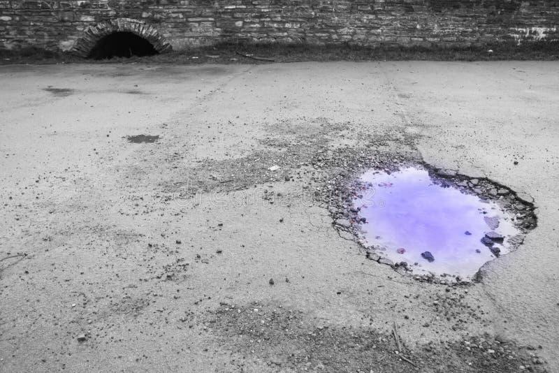 Гигантское отверстие бака в дороге с фиолетовой водой и сравнивая черно-белой предпосылкой стоковые фотографии rf
