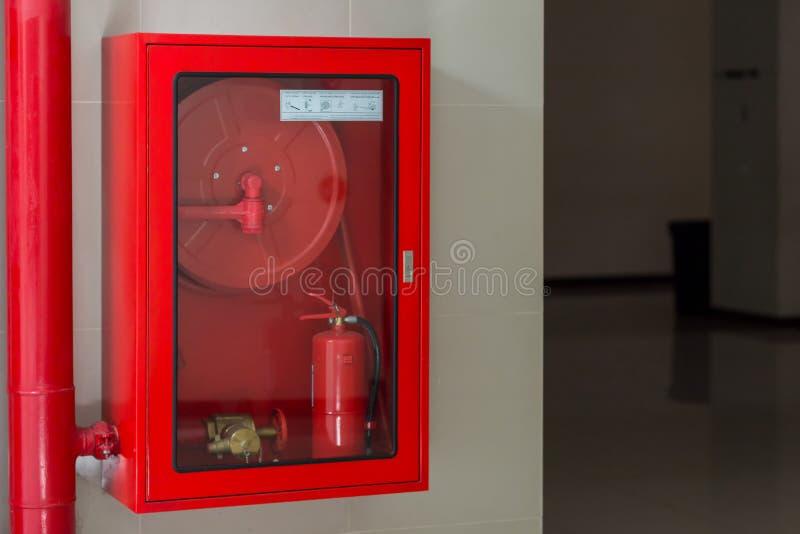 Гидрант со шлангами воды и увольнять для того чтобы потушить оборудование Оборудование пожарной безопасности в красной коробке на стоковое изображение rf
