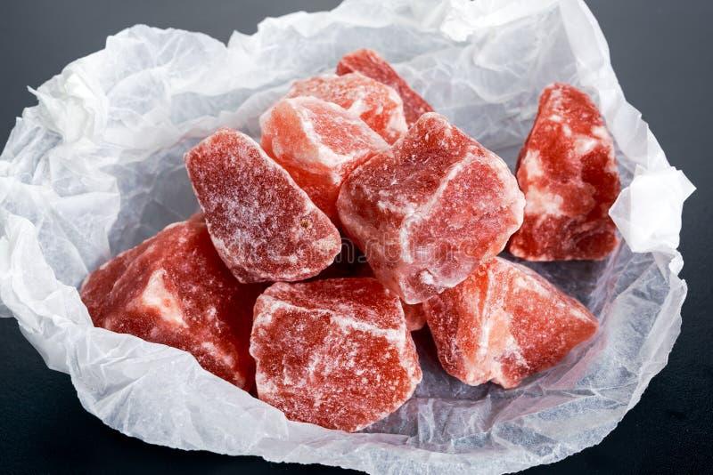 Гималайское розовое кристаллическое соль на скомканной бумаге стоковые изображения rf