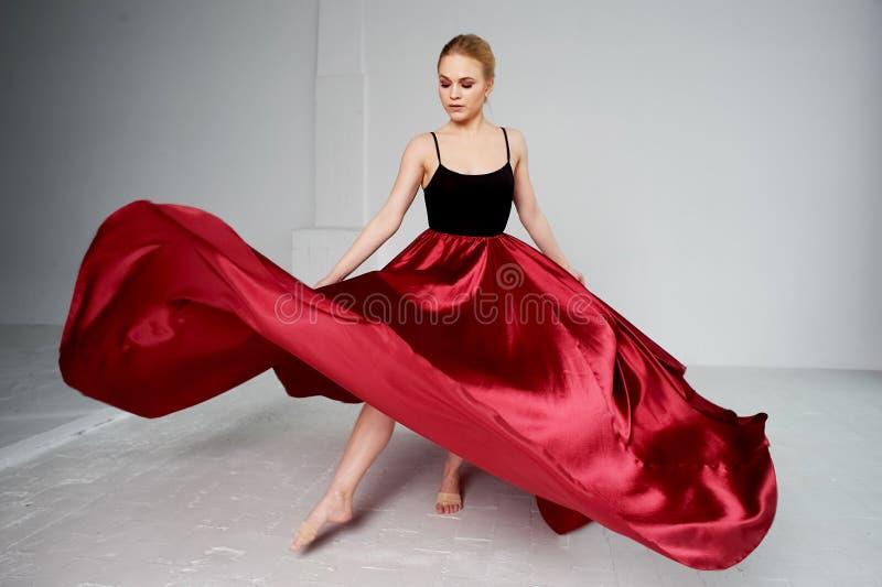 Гимнаст в темной верхней части и красной юбке шелка Цвет страсти, агрессии Танго Пластиковое тело, airiness стоковое фото